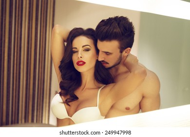 Sexy young couple in mirror at home, vintage style