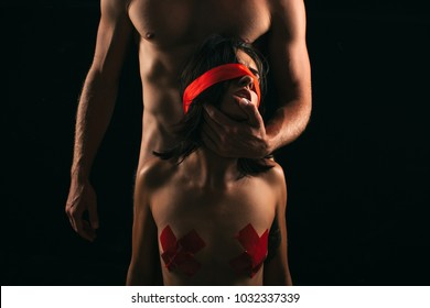 Sexy young couple of undressed sensual woman with straight body in red lace erotic lingerie sitting above muscular man kissing posing indoor on dark background, horizontal picture. Sensual sexy couple