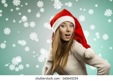 sexy young female with long smooth hair wearing warm sweater and funny red christmas hat . Winter xmas portrait