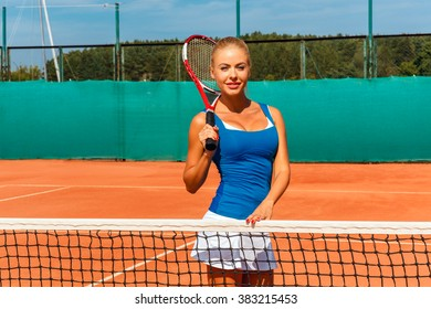 sexy young female tennis player posing with racket on a tennis court outdoors