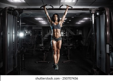 sexy young fitness girl pulls up in the gym. Brunette fitness woman in gray sport wear with perfect fitness body in gym performing abdominal exercises on the horizontal bar