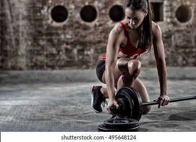 sexy young fitness woman preparing to lift some heavy weights
