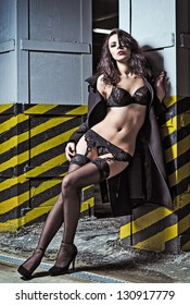Sexy young girl in black underwear and coat stands leaning against a column