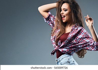 Sexy young girl with disheveled long chestnut hair wearing high waist jeans shorts and oversized knotted red and blue plaid shirt enjoys herself dancing on grey background