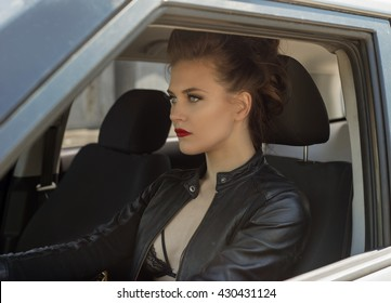 sexy young girl driving car in leather jacket and bra