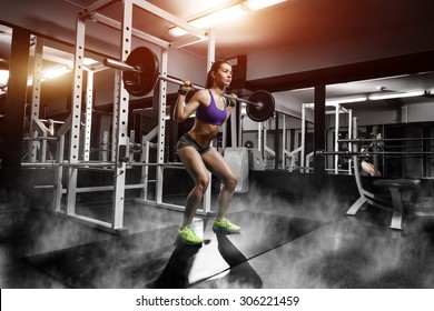 sexy young girl with perfect abs doing squat exercises. Fitness brunette fit woman in gym with barbell