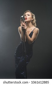 Sexy young girl singer singing in silver retro microphone on black background