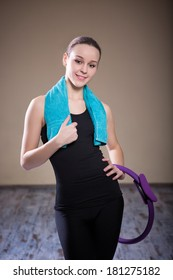 Sexy young girl standing in the studio after Pilates. Around her neck and hands holding a towel purple isotonic ring Pilates