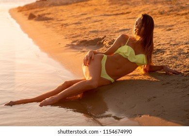 sexy young girl at sunset at the beach