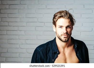 Sexy young handsome bearded man or guy with bare muscular chest in black shirt on white brick wall background, copy space