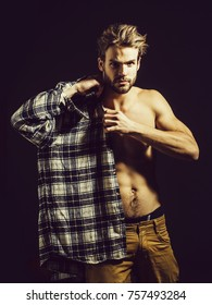 Sexy young handsome naked man with messy hair, in beige pants wears plaid shirt on dark background