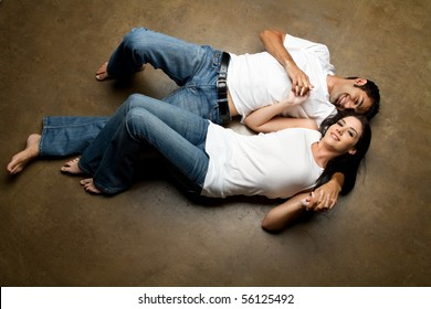 Sexy young happy casual couple relaxing on the floor