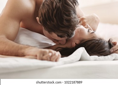 Sexy young lovers being intimate in bed, closeup