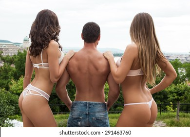 Sexy young macho man with women posing outdoor