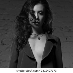 Sexy young makeup beautiful model with curly hair and burgundy lipstick posing in grey style suit clothing on studio background. Black and white. Art mystic portrait