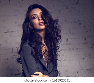 Sexy young makeup beautiful model with curly hair and burgundy lipstick posing in grey style suit clothing on studio background. Toned color portrait. Closeup