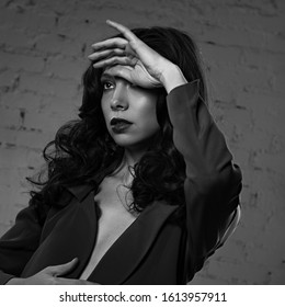 Sexy young makeup beautiful model with curly hair and burgundy lipstick posing in grey style suit clothing on studio background. Art. Black and white