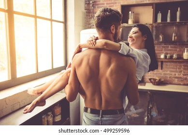 Sexy young man with bare torso is holding his beautiful girlfriend in arms while standing in kitchen at home. Both are looking at each other and smiling