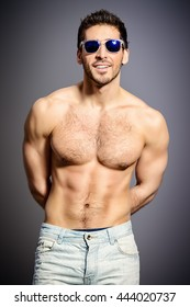 Sexy young man with beautiful muscular body looking to camera and smiling invitingly. Studio shot.