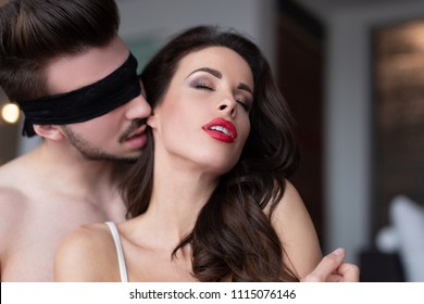 Sexy young man in blindfold whispering to lover, indoors