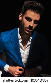sexy young man buttoning his suit , dramatic picture in studio on dark background