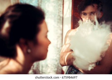 Sexy young man with his beautiful girlfriend standing in kitchen at home talking by the window. Both are looking at each other and guy Smoking