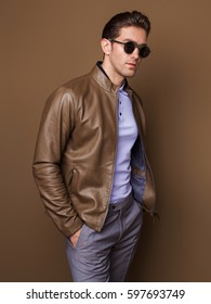 Sexy young man in a leather jacket and dark glasses. He is dressed in a polo-neck, a brown leather jacket, gray trousers, dark glasses costs on a brown background