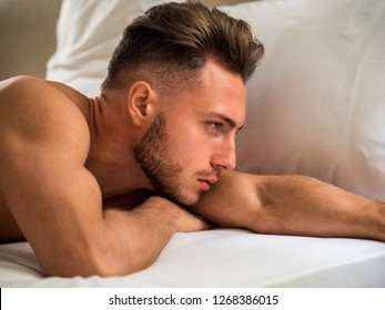 Sexy young man with muscular body on bed looking away, profile shot