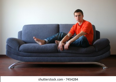 Sexy young man in an orange t-shirt sitting on the sofa