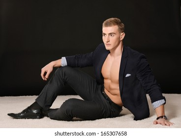 Sexy young man portrait on black background