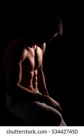 Sexy young man shirtless sitting, dark background