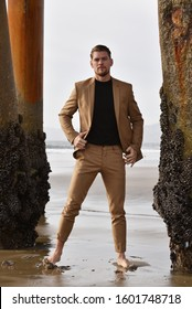 Sexy young man in a suit under the pier at Venice Beach California