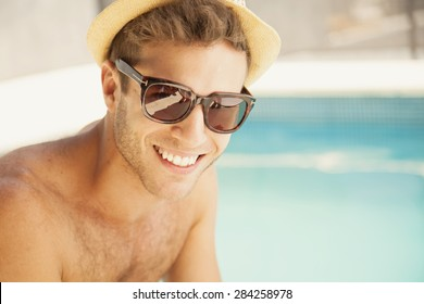 Sexy young man sunbathing by poolside with sunglasses
