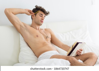 Sexy young man in underwear reading a book in bed.