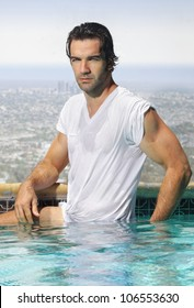 Sexy young man in wet t-shirt in swimming pool overlooking city view