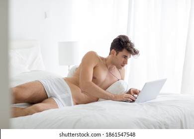 Sexy young man working on a laptop computer lying in bed wearing underwear during the day.