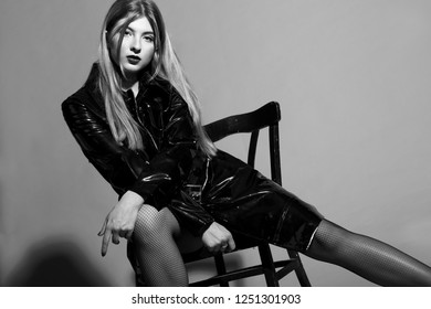Sexy young model in black fashion coat and tights.On chair. Studio shot . Black and white.Fashion.Grey background.Posing.Passion.