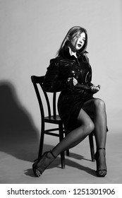 Sexy young model in black fashion coat and tights.Posing on chair. Studio shot . Black and white.Fashion.Grey background.Posing.Passion.Closeup.