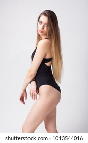 Sexy young model woman with long blonde hair posing in the studio isolated on white background dressed in black swimwear