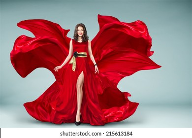 Sexy young motion woman in long red evening fluttering fashion dress flying over background