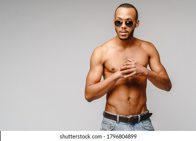 Sexy young muscular african american man shirtless wearing sunglasses over light grey background