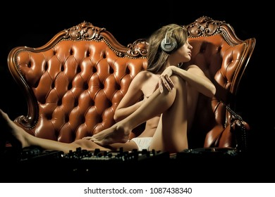 Sexy young naked dj woman in white panties and headphones with bare chest and nipples sitting at table with mixer console on brown leather royal sofa in night club, horizontal picture