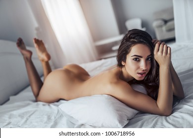 Sexy young naked woman is lying in white bed.