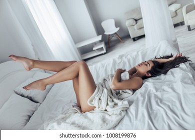 Sexy young naked woman is lying in white bed covered by blanket.