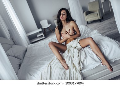 Sexy young naked woman is sitting on white bed covered by blanket.