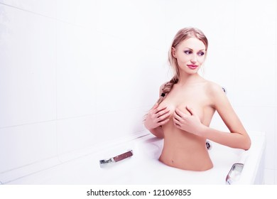 sexy young nude blond woman taking a bath