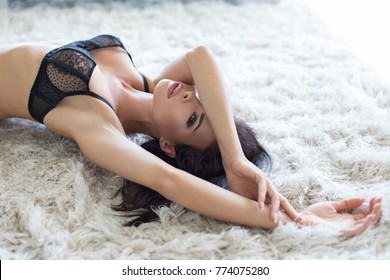 Sexy young passionate brunette woman in bra posing on carpet