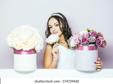 Sexy young pretty woman or cute smiling girl with crown on head, has long hair in white dress with lilac rose and peony flowers, bouquet boxes on violet background