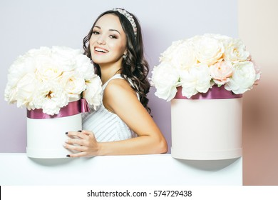 Sexy young pretty woman or cute smiling girl with crown on head, has long hair in white dress with lilac rose and peony flowers, bouquet boxes on pink background