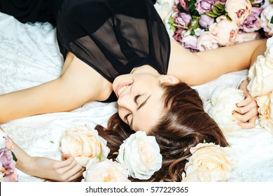 Sexy young pretty woman or cute smiling girl with long hair in black dress laying among lilac rose and peony flowers on white bedsheet
